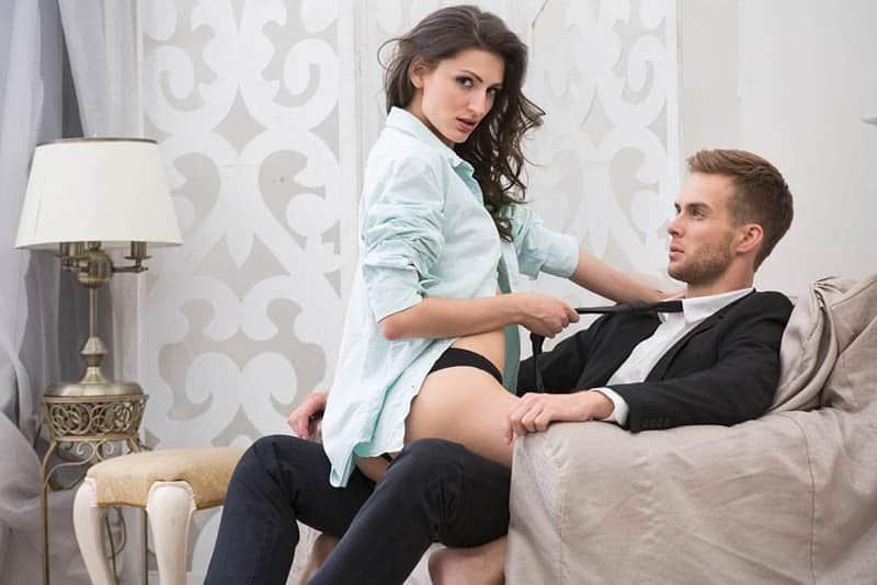 Frau in Unterwäsche sitzt auf Mann mit Anzug auf Sofa