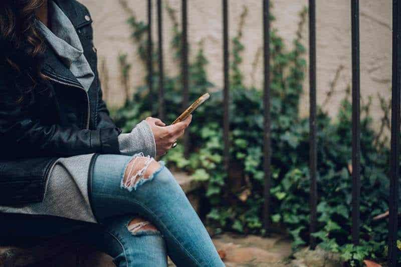 Frau mit gekreuzten Beinen, die auf ihrem Telefon tippt