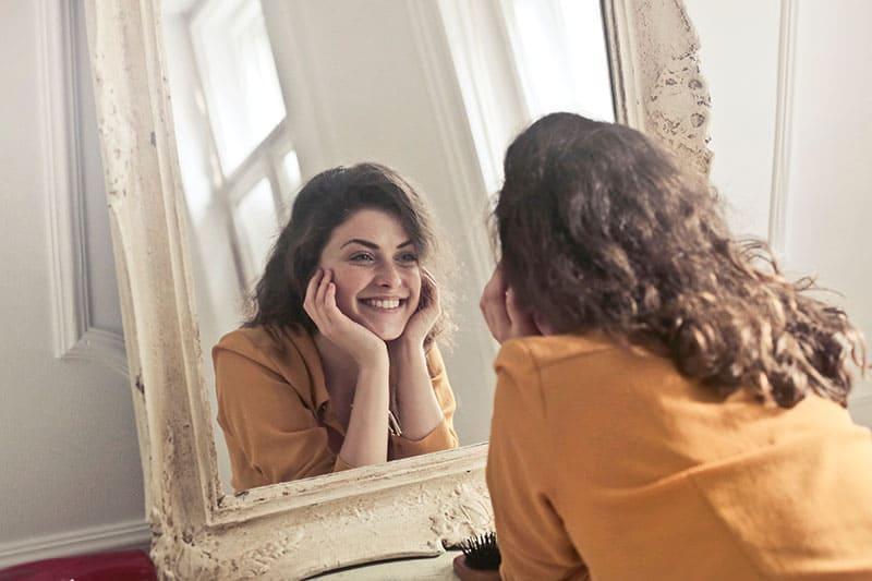 Frau schaut sich im Spiegel an