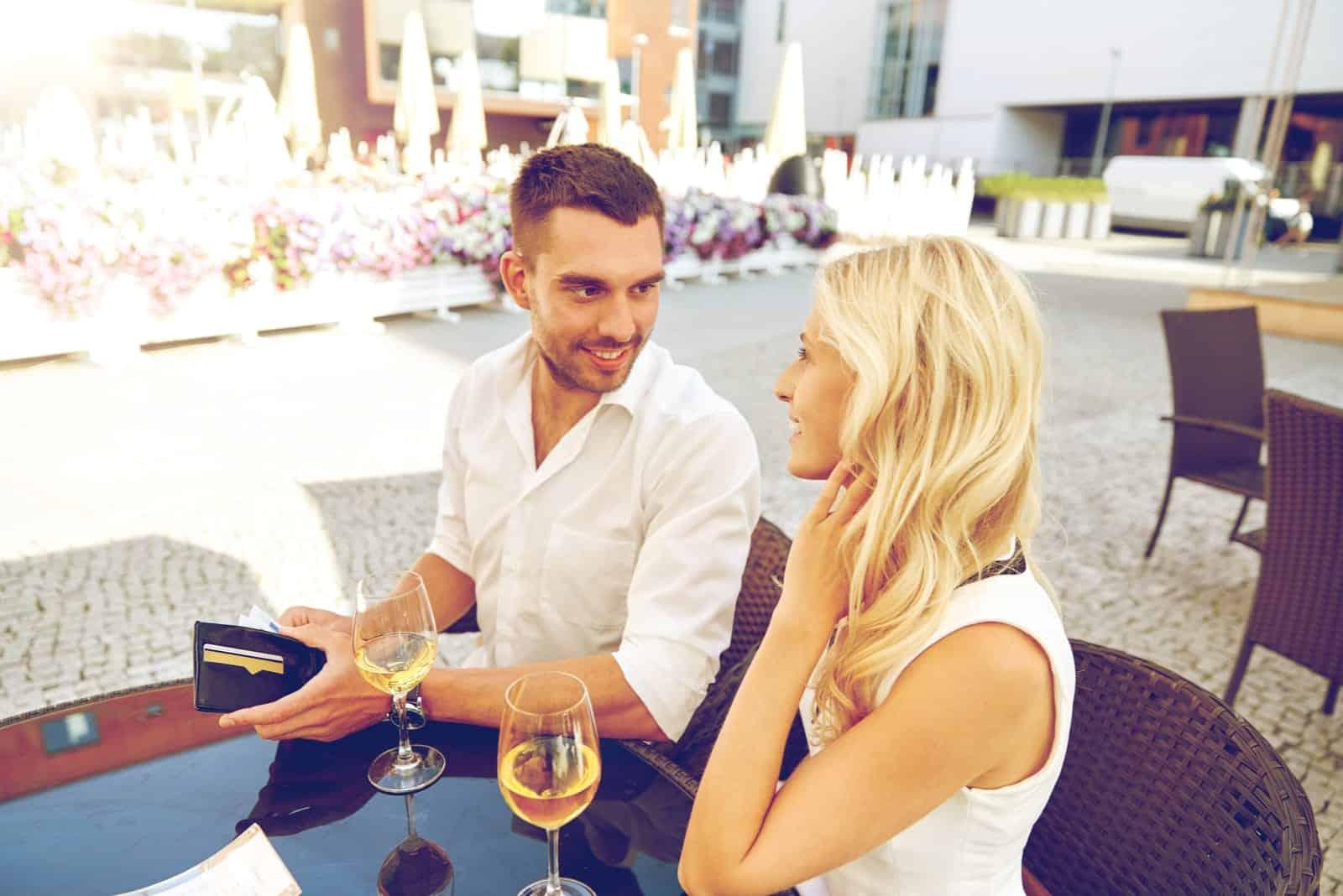 Glückliches Paar mit Brieftasche und Weingläsern, das die Rechnung im Restaurant bezahlt
