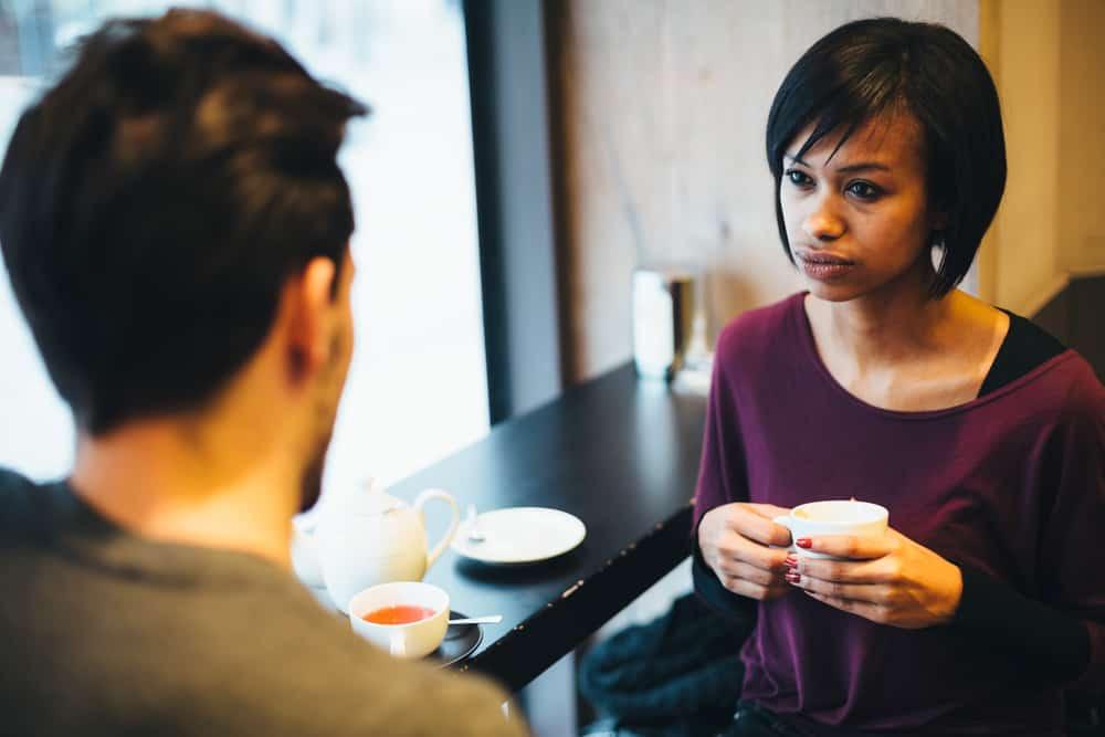 Hinter der Bar am Fenster im Café sitzt ein Paar und redet