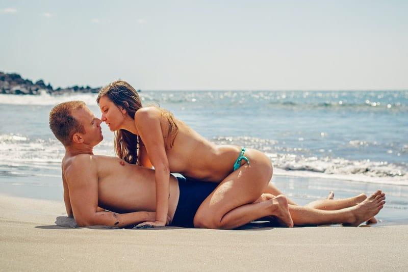 Liebespaar am Strand liegen und küssen