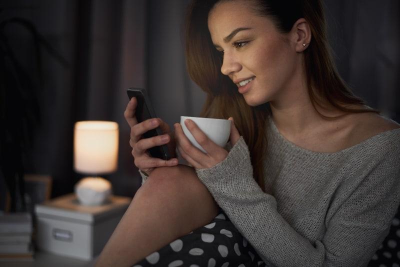 Mädchen sitzt im Bett in der Nacht und Knopf auf dem Handy