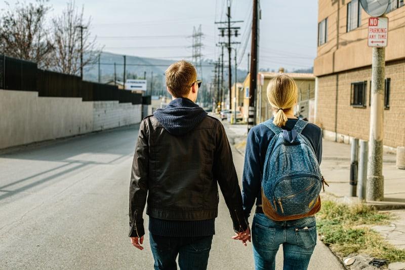 Mann, der Hände der Frau hält, geht auf Betonstraße