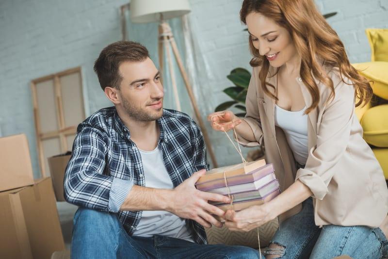 Mann hilft lächelnde Frau mit ihren Büchern