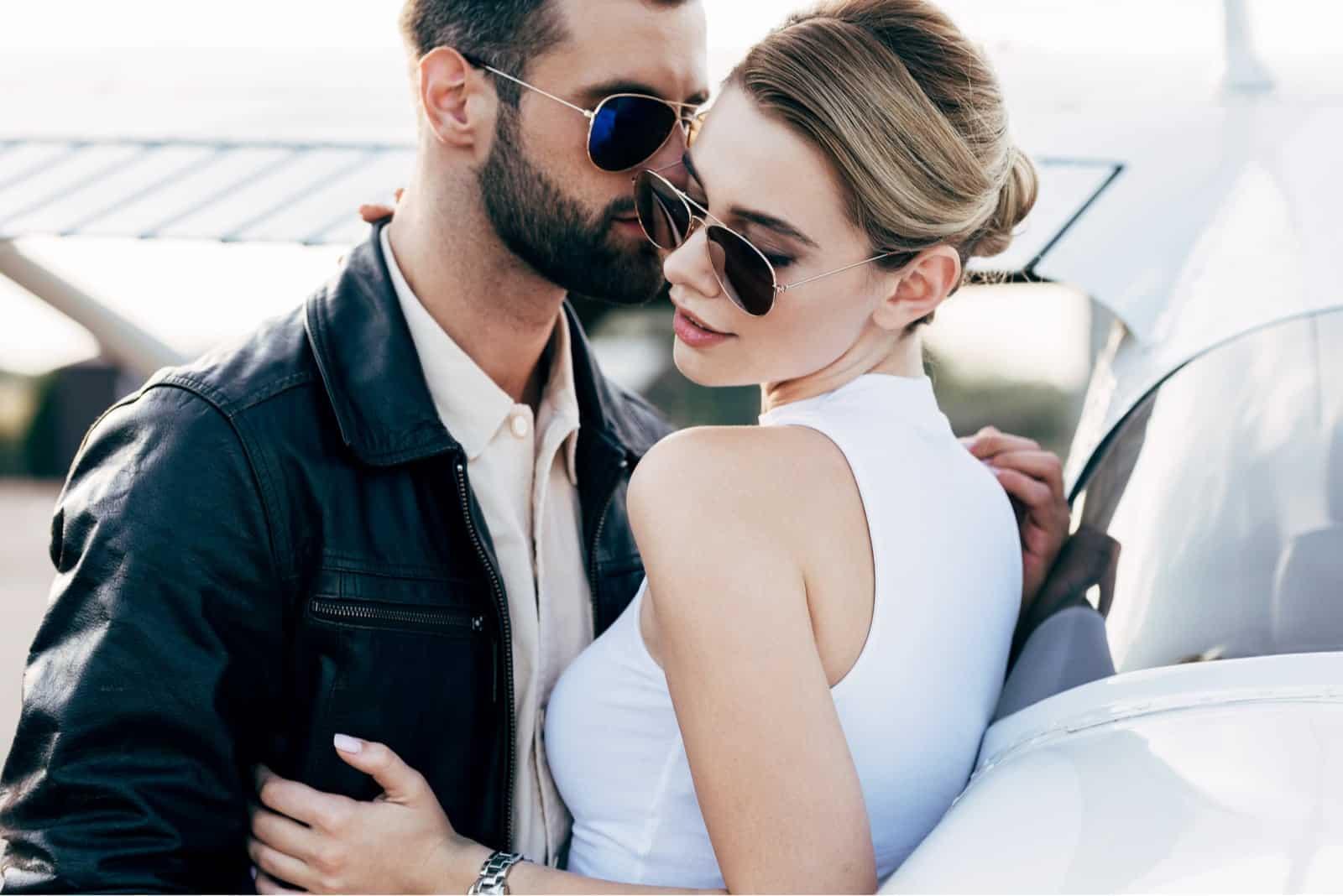 Mann-in-Leder-Jacke-und-Sonnenbrille-umarmen-attraktive-Freundin