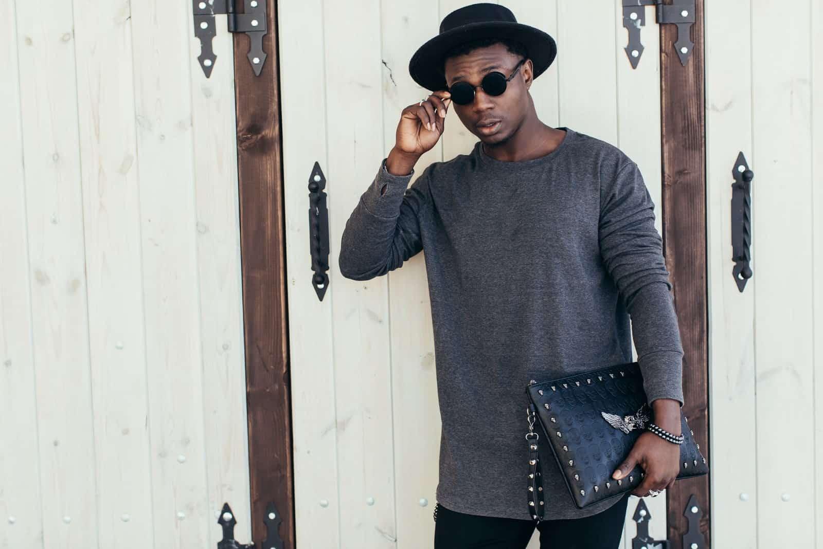 Mann mit Sonnenbrille und Hut in der Nähe einer Wand