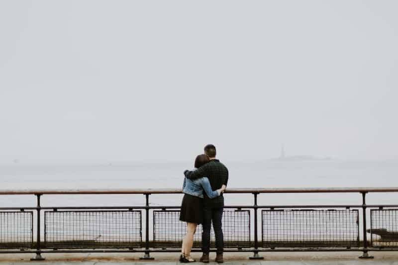 Paar, das vor Zaun nahe Gewässern steht