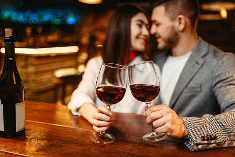 Paar hält ein Glas Wein in der Bar