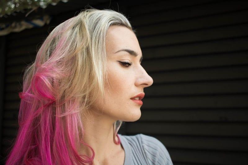 Porträt einer Blondine mit rosa Strängen