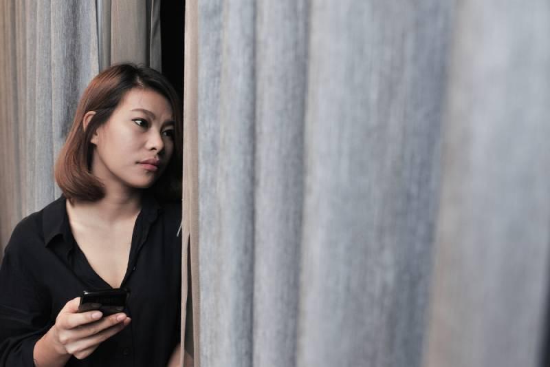 besorgte Frau, die Telefon hält und nach draußen schaut