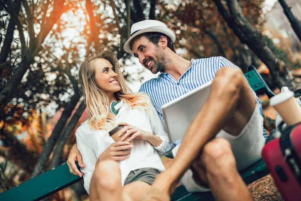 ein attraktives lächelndes Paar, das auf einer Parkbank sitzt