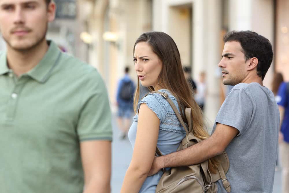 ein eifersüchtiger Mann und eine Frau, die einen anderen Mann ansehen