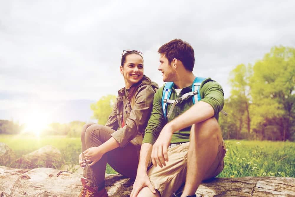ein lächelndes Liebespaar, das in der Natur sitzt und spricht