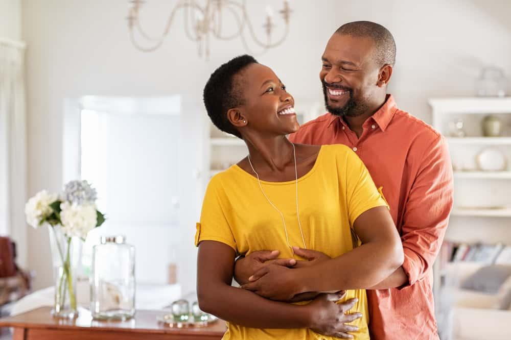 ein lächelndes liebendes schwarzes Paar, das in einer Umarmung in der Küche steht