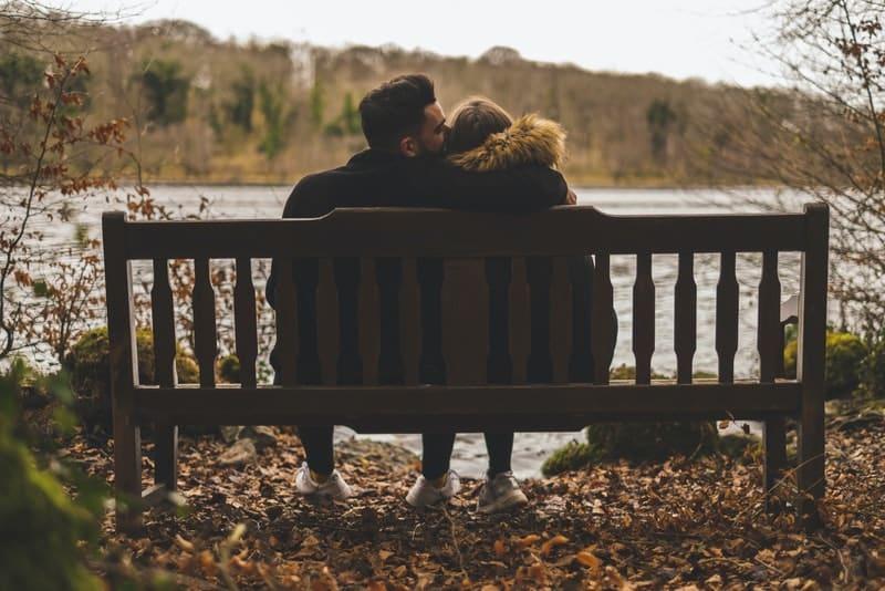 ein liebendes Paar am Ufer eines Flusses, das in einer Umarmung auf einer Bank sitzt