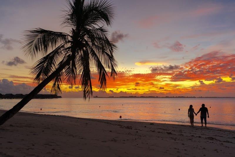 ein liebendes Paar, das bei Sonnenuntergang an einem Sandstrand am Meer spaziert