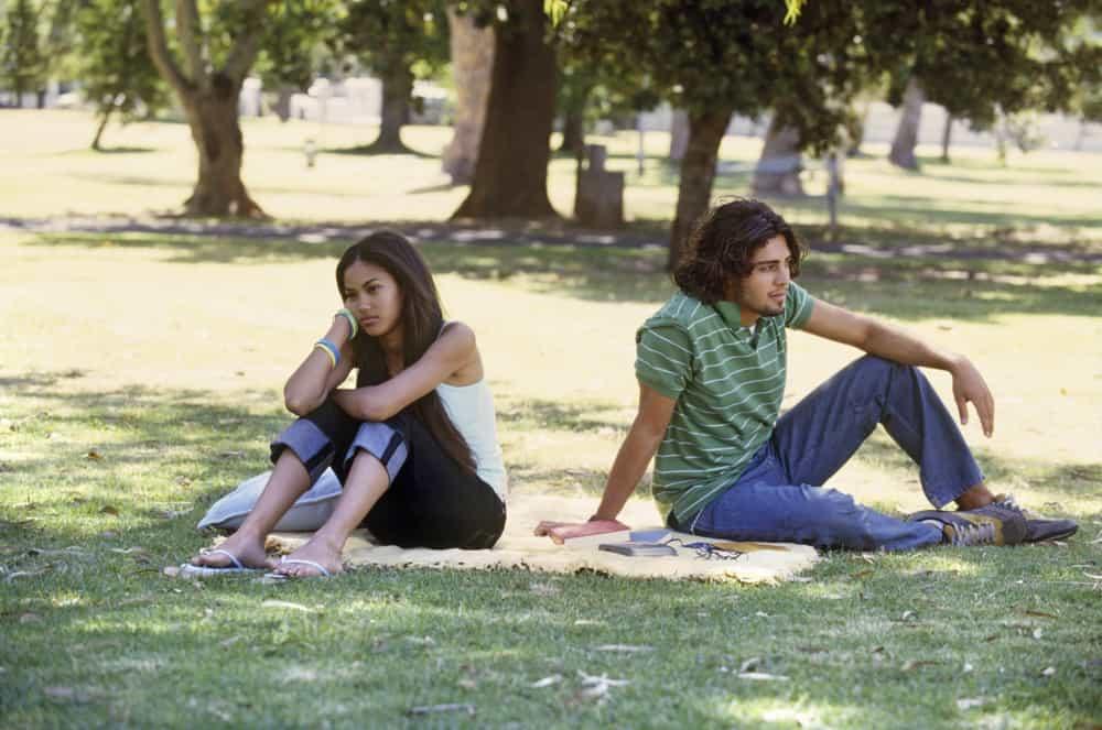 ein liebevolles Paar, das mit dem Rücken zueinander im Gras sitzt