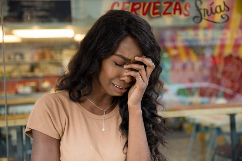 ein trauriges Mädchen, das vor dem Laden weint