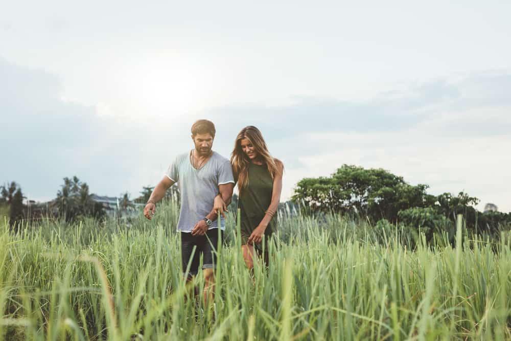 ein verliebtes Paar, das über ein Grasfeld geht