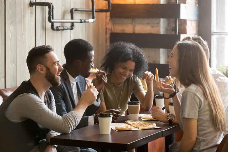 eine Gruppe von Freunden, die Pizza in einer Pizzeria essen