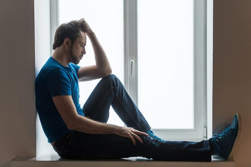 einsamer Mann am Fenster sitzen