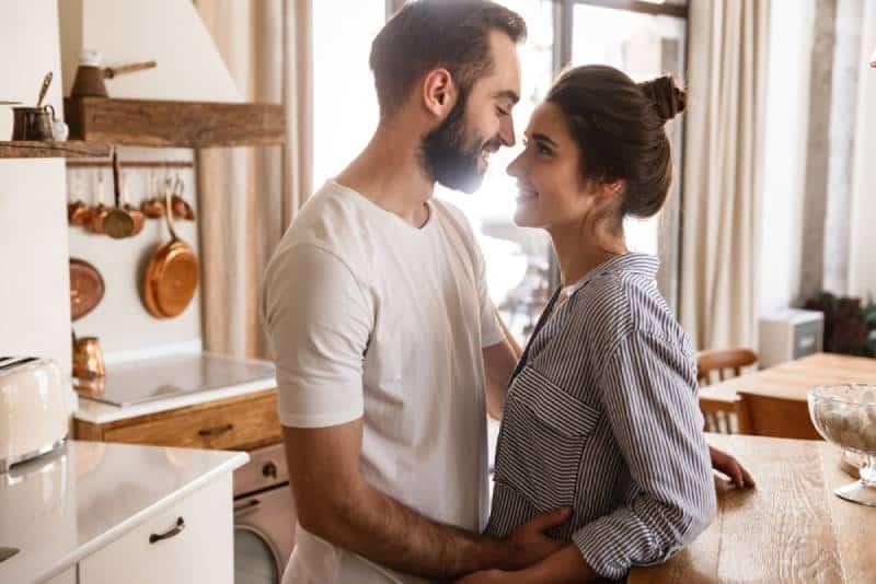 entzückendes brünettes Paar, das lächelt, während es zu Hause zusammen umarmt
