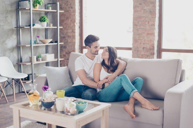 glückliches Paar, das im Wohnzimmer umarmt
