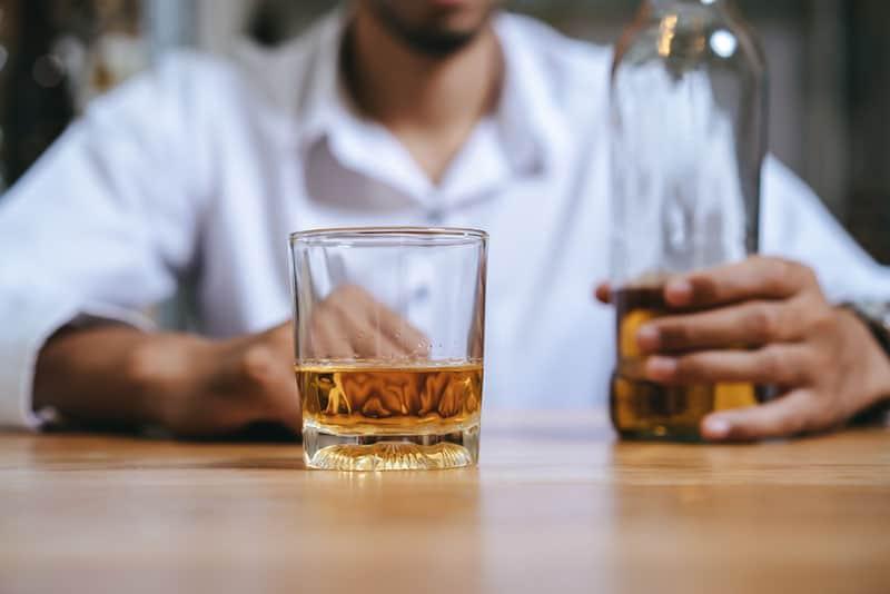 junger Mann, der Alkohol trinkt