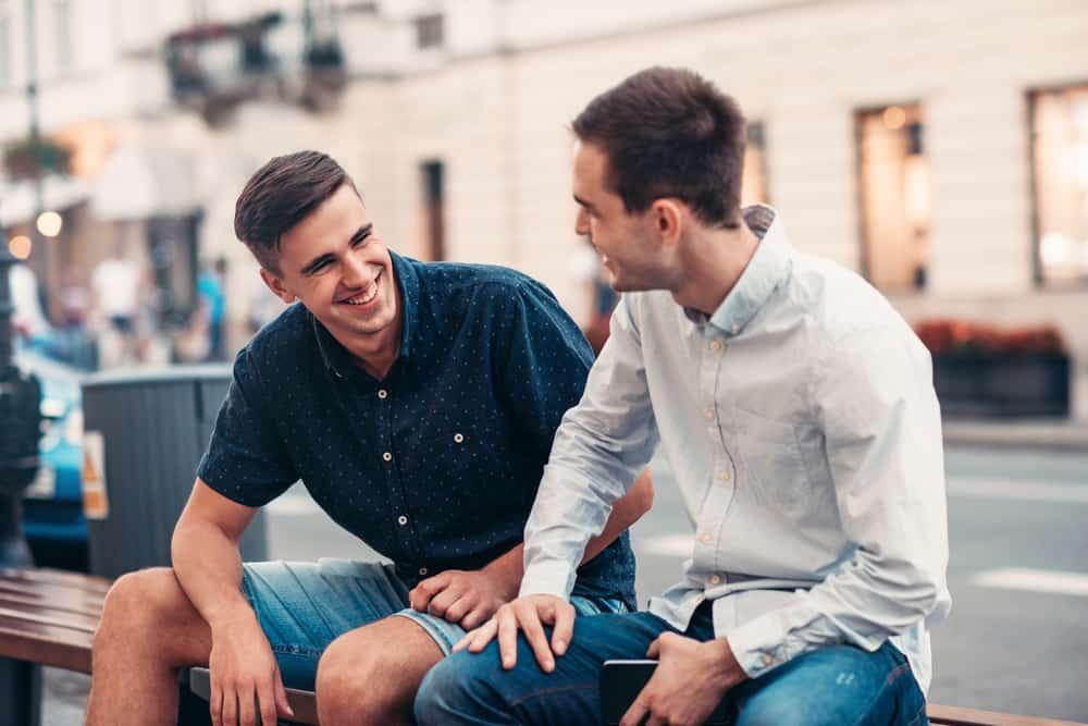 lächelnd sitzen zwei freunde auf einer bank und unterhalten sich