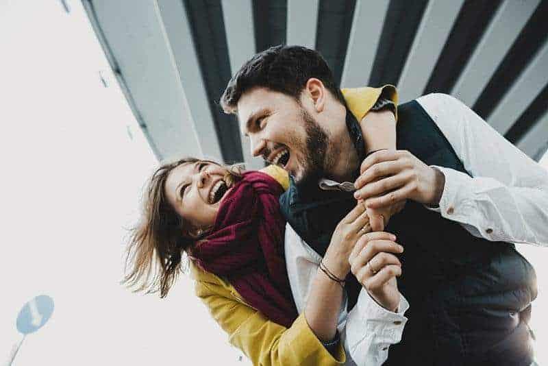 lächelnde Frau, die Mann draußen umarmt