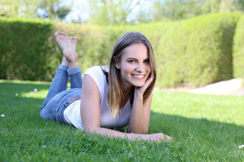 lächelnde Frau, die auf Rasen liegt