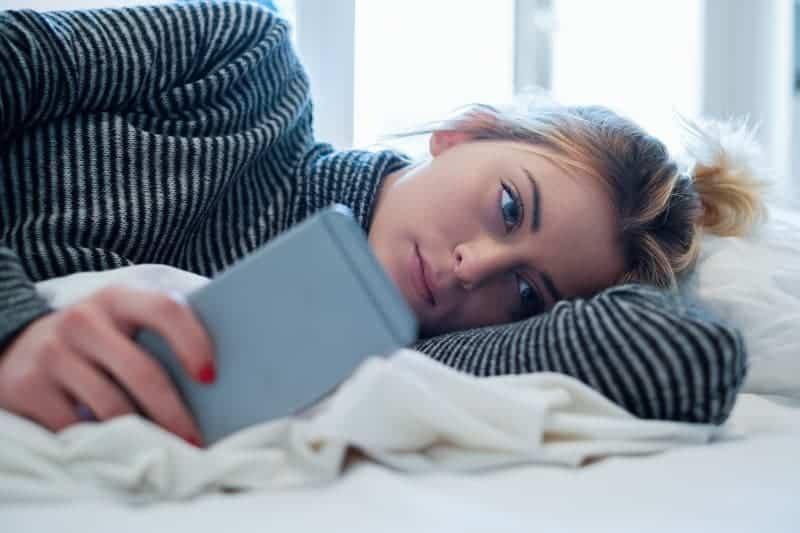 nachdenkliche Frau, die auf dem Bett liegt und auf ihrem Telefon tippt