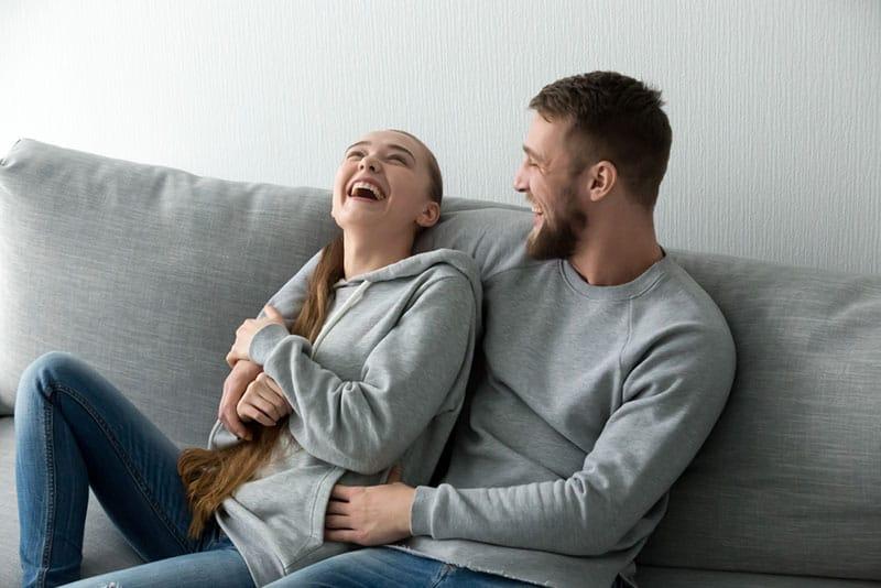 schönes Paar lacht im Wohnzimmer