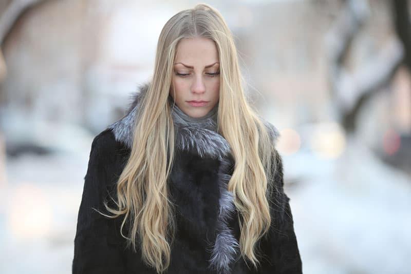 traurige blonde Frau mit langen blonden Haaren zu Fuß