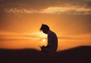 Mann, der vor Sonnenuntergang steht