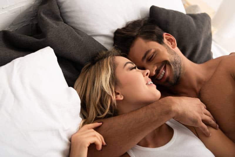 lächelndes zartes Paar, das morgens im Bett umarmt
