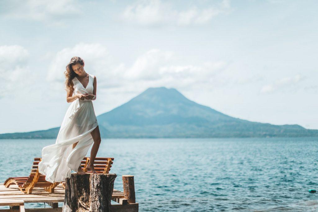 Auf dem Pier steht eine hübsche Frau in einem sexy weißen Kleid