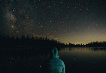 Der junge Mann sitzt am Flussufer