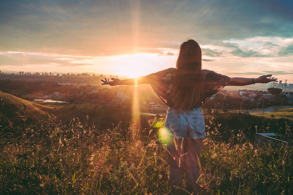 Das Mädchen steht mit ausgestreckten Armen und gedrehtem Rücken auf einem Feld