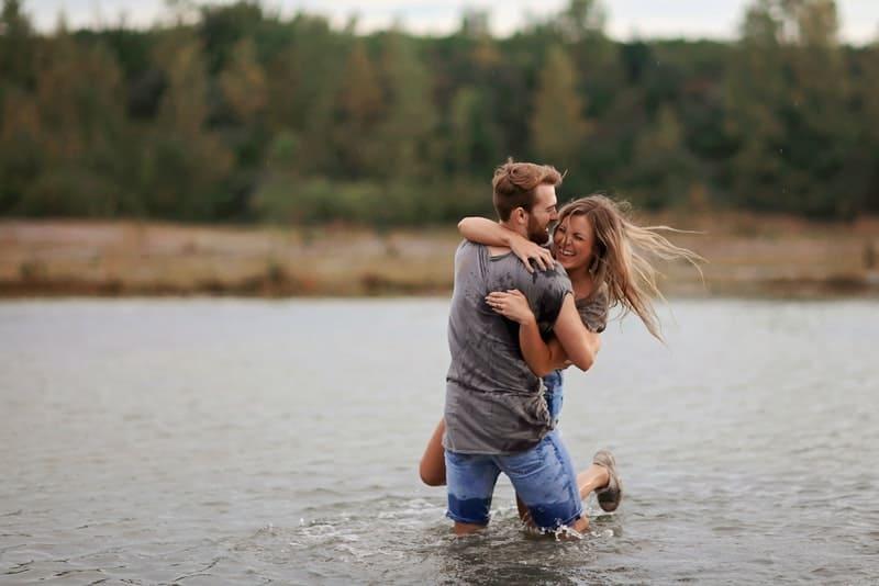 Das glückliche Paar steht im Fluss umarmt