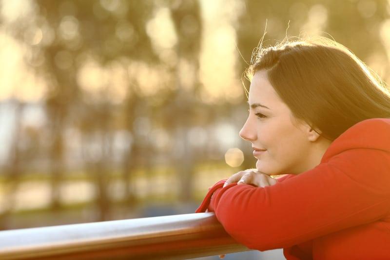 Das junge Mädchen lacht, als sie an schöne Dinge denkt