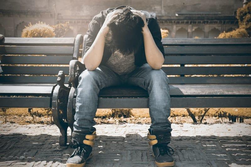 Der unglückliche Mann sitzt auf einer Bank und behält den Kopf