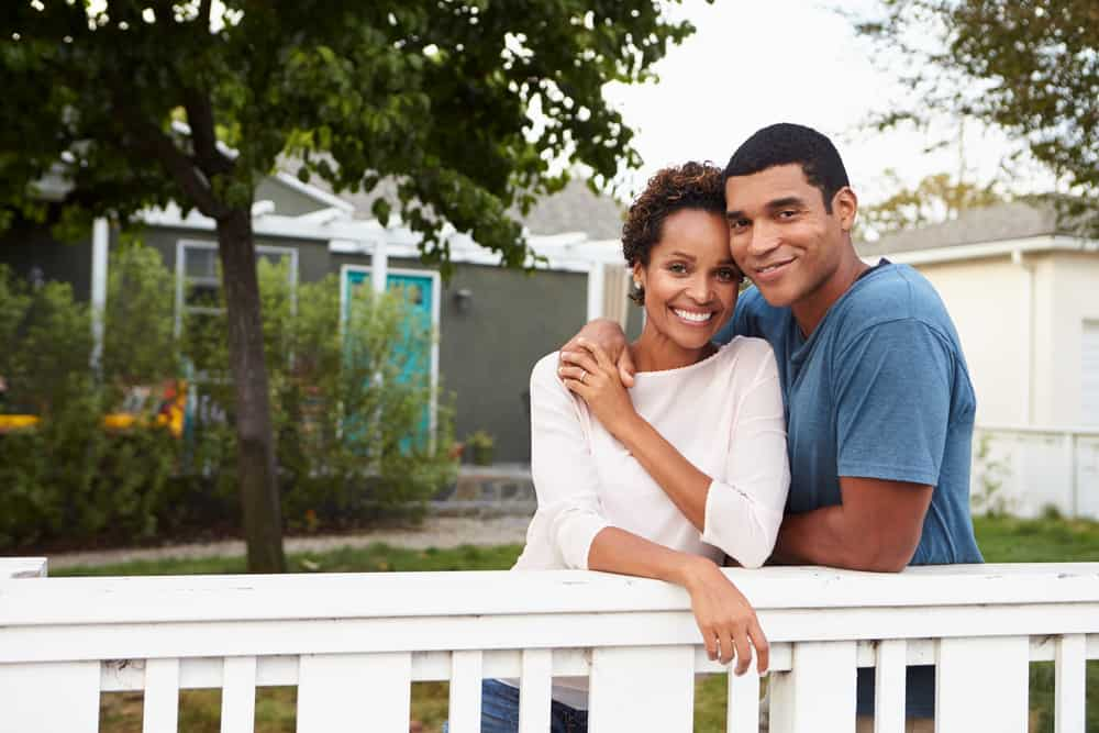 Draußen, neben einem weißen Zaun, umarmen sich ein schwarzer Mann und eine schwarze Frau