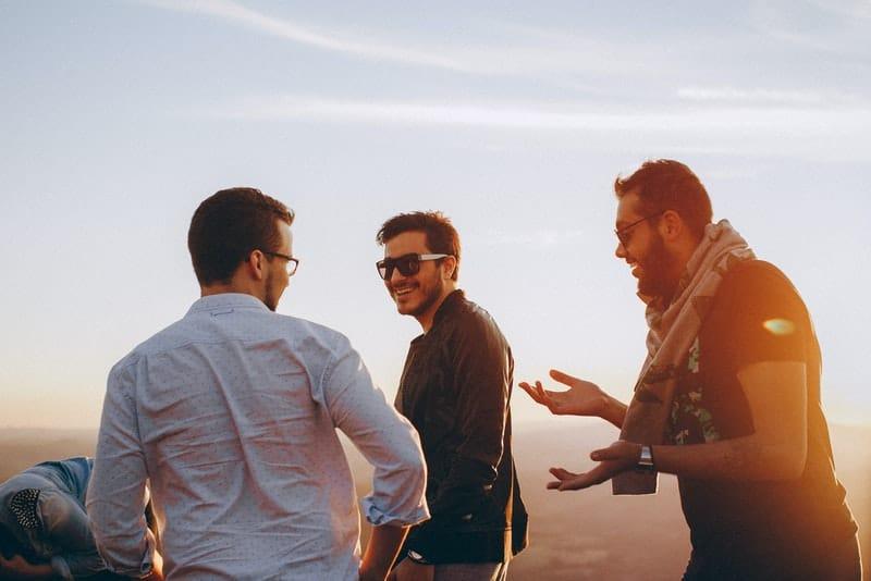 Drei Freunde unterhalten sich mit einem Lächeln