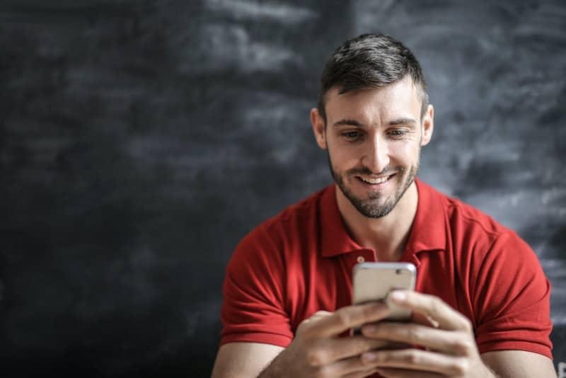 Ein überglücklicher Mann mit Bart in einem roten T-Shirt liest eine Nachricht auf seinem Handy
