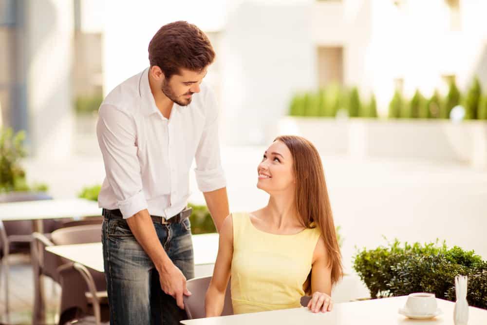 Ein Herr in einem weißen Hemd hilft seiner Frau, sich zu setzen