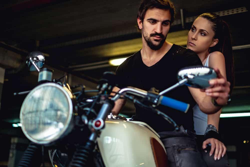 Ein Mann auf einem Motorrad sieht seine Frau im Rückspiegel an