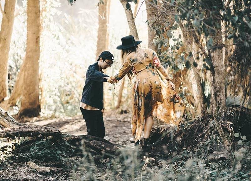 Ein Mann hält die Hand einer Frau im Wald