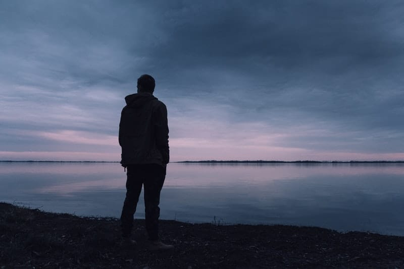 Ein Mann in der Abenddämmerung steht am Ufer des Meeres